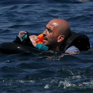 Refugiado segura bebê após naufrágio da embarcação que os levava para a ilha de Lesbos