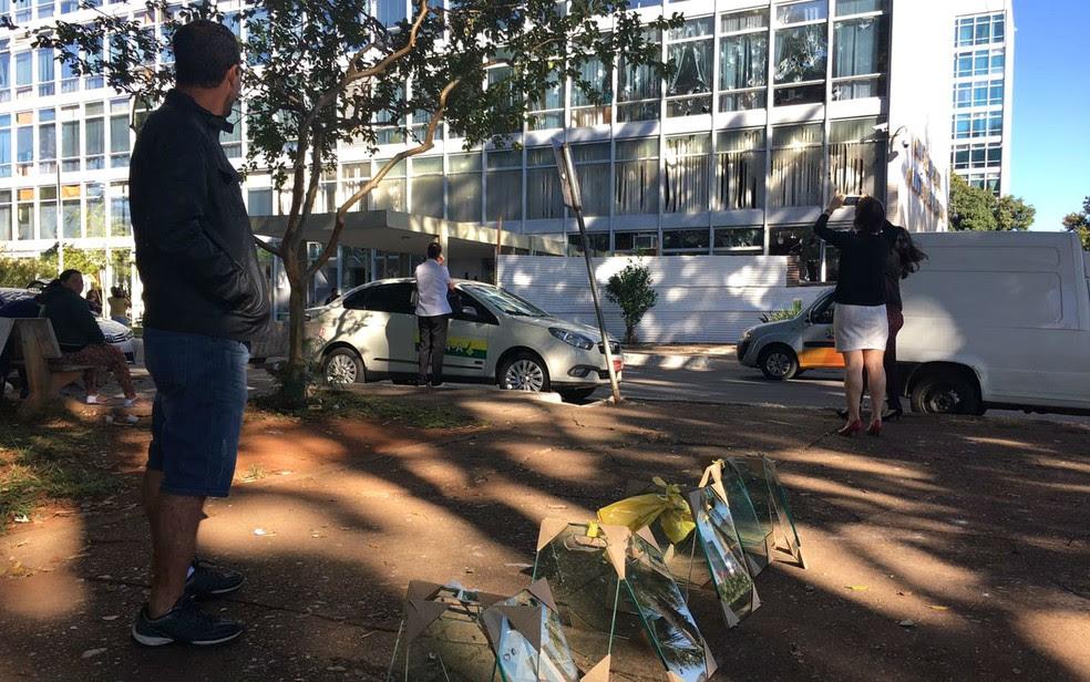 Ambulante vende tábuas de vidro ao lado de ministério que teve os vidros quebrados durante manifestação contra governo Temer (Foto: Luiza Garonce/G1)