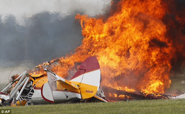 Wreckage: The bi-plane hit the ground and burst into flames, instantly killing the pilot and performer