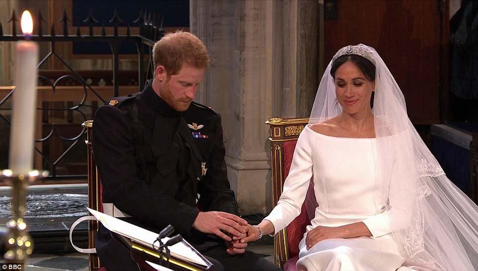 Harry acaricia la mano de su sonriente novia Meghan en la capilla de San Jorge en Windsor durante la boda real
