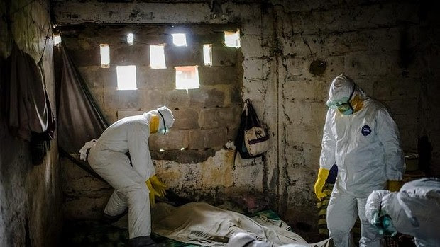 Members of an Ebola burial team collect the body of a suspected Ebola victim from a home in Monrovia, Liberia.