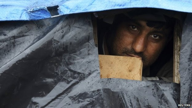 An Afghan migrant looks out the window of his makeshift shelter at the harbour in Calais