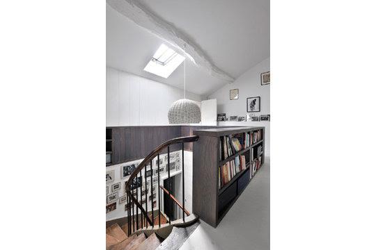 Montée d'escaliers tapissée de photos et garde-corps bibliothèque.