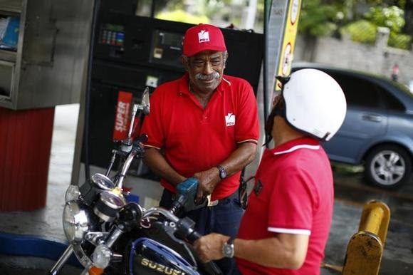 A man pumps gasoline at a service station in Caracas August 7, 2014. REUTERS/Jorge Silva/Files
