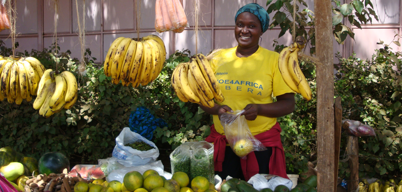 Photo of a woman selling fruit at a fruit stand.