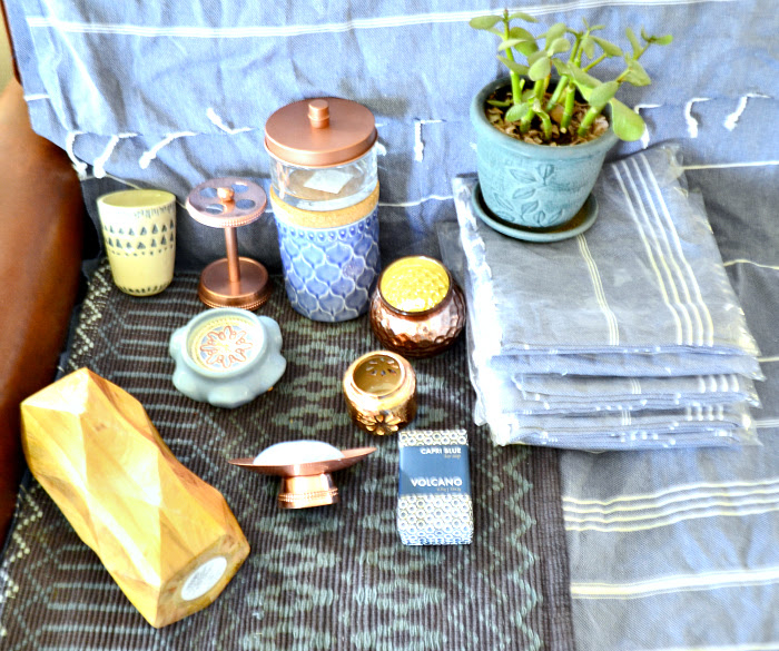 Copper candle holders are Target dollar spot. Copper soap dish and toothbrush holder are Wayfair, Wooden faceted vase, glass lidded jar with copper top (was chrome, spray painted it to match) are Target. Cream tumbler with indigo tribal design, blue jar with cork lid, footed candle and Volcano soap are Anthropologie, the turkish towels are Amazon. The jade plant and pot are a gift from my mom. The rug beneath the decor is Target, clearanced out many months ago from the Threshold line.