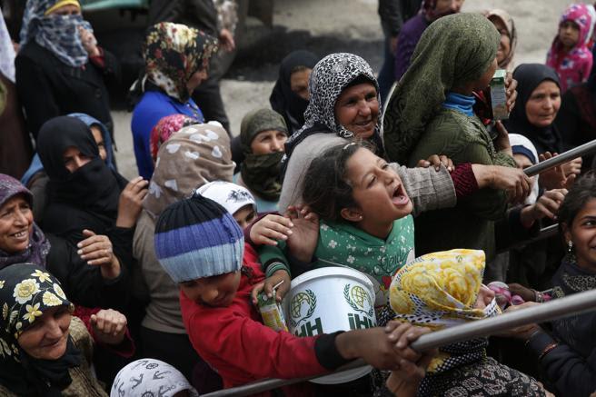Una multitud se agolpa para una distribución de alimentos en la ciudad de Afrin, el 24 de marzo