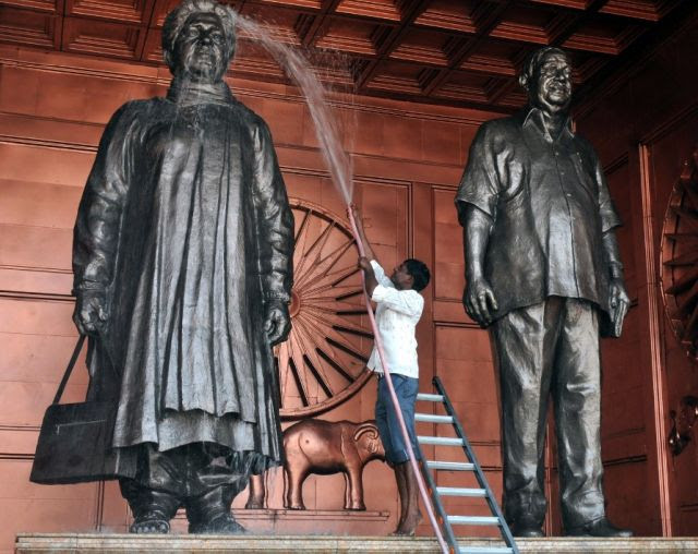 A labourer washes a statue of the Bahujan Samaj Party leader Mayawati and BSP founder Kashi Ram in Lucknow. AFP