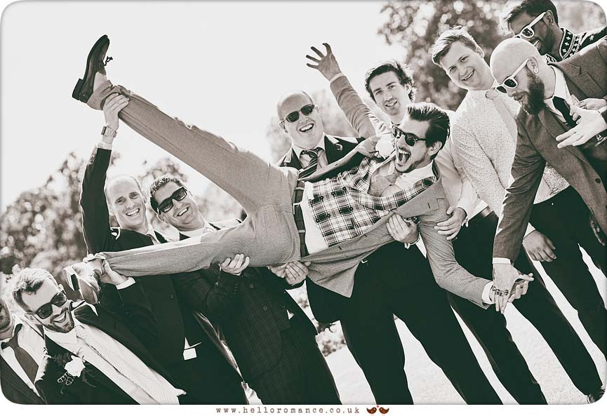 Groom being held upside down by groomsmen and ushers - www.helloromance.co.uk