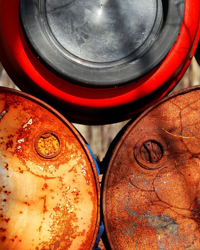 The space between three brightly rusting barrels.