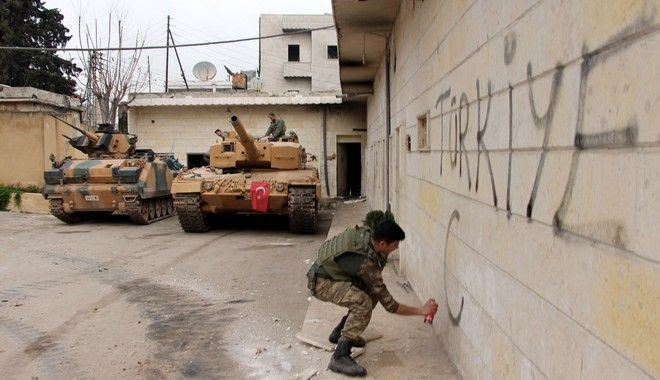 "A Turkish soldier writes ""Turkey"" on a wall, near to tanks in position, in the city center of Afrin, northwestern Syria, Sunday, March 18, 2018. Turkey's president said Sunday the Turkish military and allied Syrian forces have taken ""total"" control of the town center of Afrin, a major development in the nearly two-months offensive against a Syrian Kurdish militia that controls the area. (Hasan Krmzita/DHA-Depo Photos via AP)"