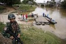 A soldier stands guard on the Thai side of the river as people prepare to cross into Malaysia in Sungai Kolok in southern Narathiwat province