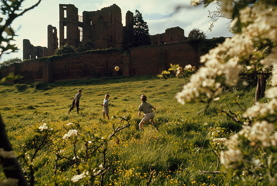Young boys throw a ball on a lush green hillside below castle ruins in Warwickshire, England, 1968.Photograph by Ted Spiegel, National Geographic