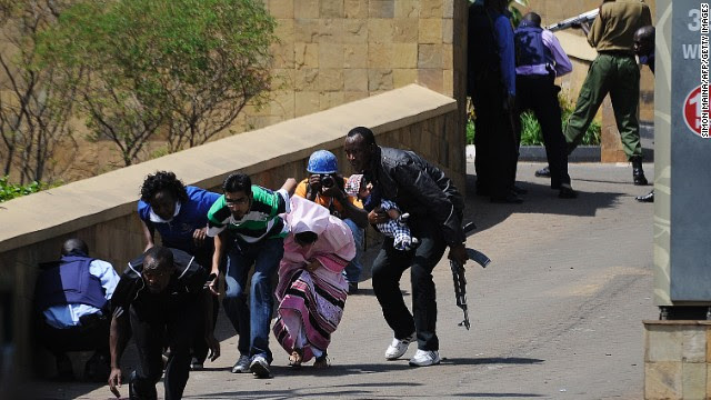 A police officer carries a baby as people keep low and run to safety. Crowds dashed down the streets as soldiers in military fatigues, guns cocked, crawled under cars to get closer to the mall.