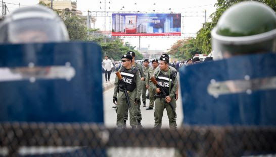 Police armed with tear gas and riot gear block the road in Phnom Penh's Meanchey district yesterday as CNRP supporters try to make their way to the Royal Palace.