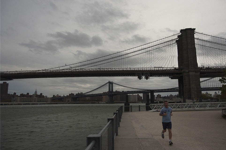 Calm before the storm: A man jogs along Brooklyn Promenade as clouds move over Brooklyn Bridge in New York on Sunday morning