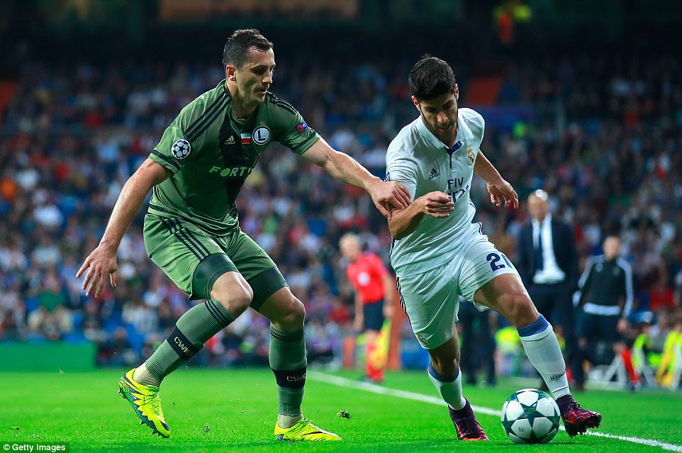 Full-back Jakub Rzezniczak puts Asensio under pressure near the touchline as both benches watch on in the distance
