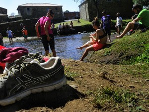 Peregrinos descansam e tomam banho em rio a 40 km de Santiago (Foto: Miguel Riopa/AFP)