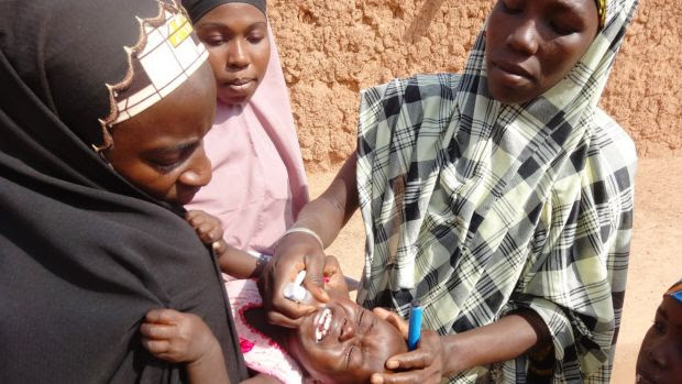A polio vaccinator giving a child the vaccine in northern Nigeria in 2013.