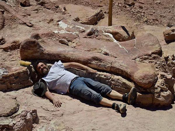 Homem ao lado do osso encontrado