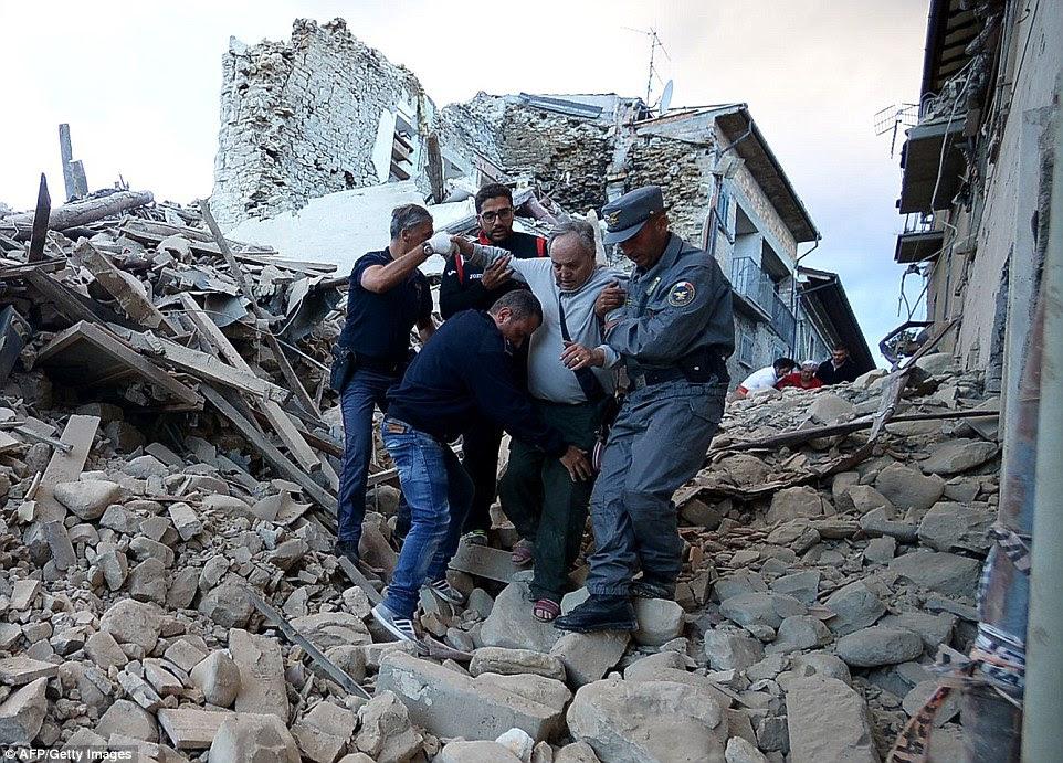 Equipes de emergência ajudam um homem idoso, ferido à segurança nas Amatrice, onde muitos são acreditados para ser preso sob os escombros