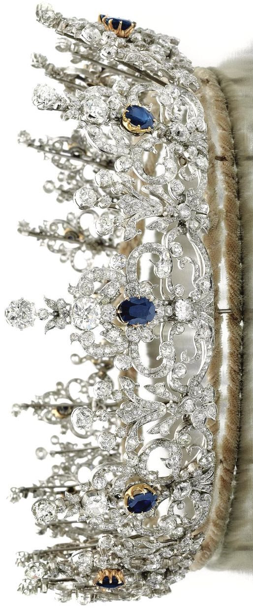 Sapphire and diamond tiara, 1900s Designed as a series of thirteen graduated stylised ribbon and scroll elements, set with circular-, single-cut, cushion-shaped and oval diamonds, each highlighted at the centre with an oval sapphire, inner circumference approximately 485mm.