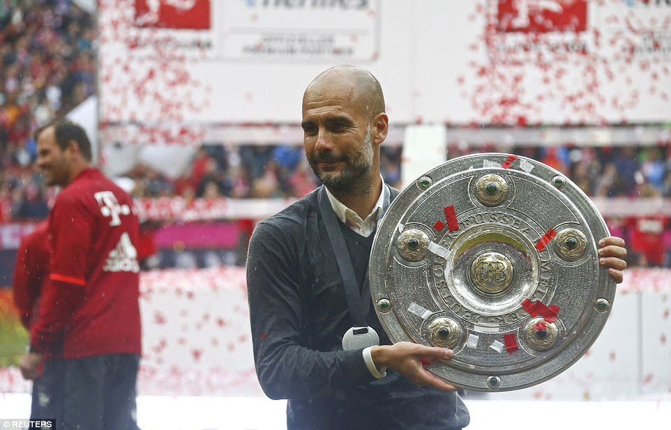 Pep Guardiola gets his hands on the trophy before he leaves the German giants after three-and-half years in charge