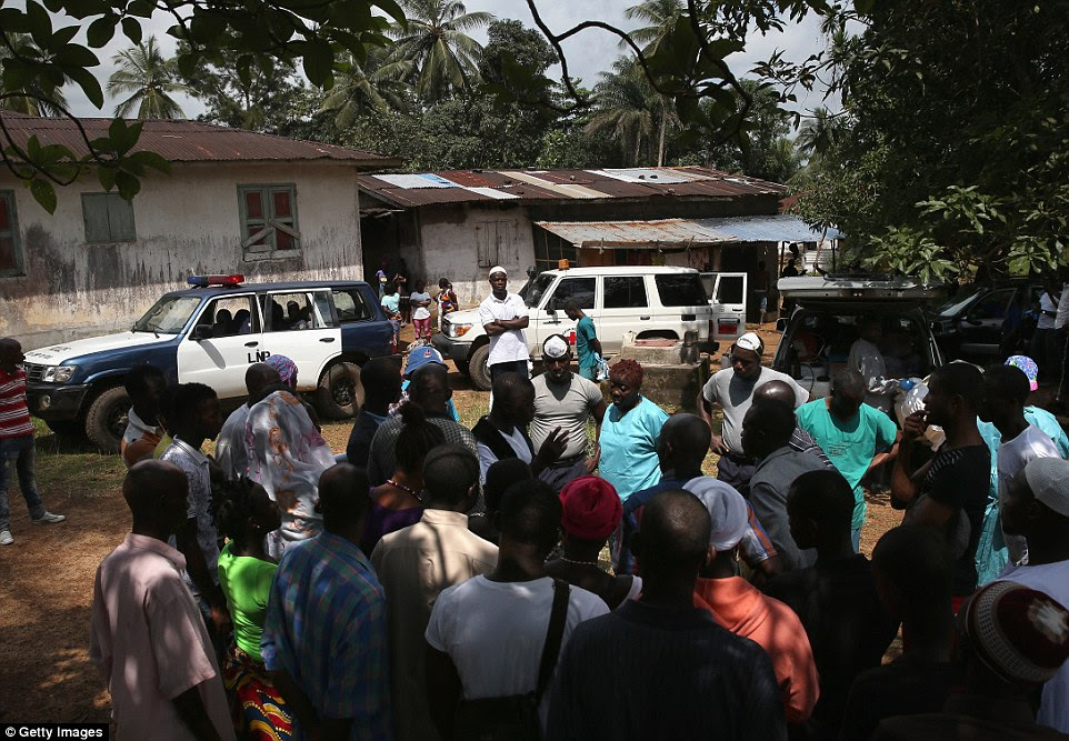 Action: Family members and neighbors try to convince an Ebola burial team not to take away the body of Nama Fambule for cremation