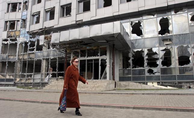 Uma mulher passa por um edifício danificado lutando em Donetsk, 15 de abril de 2015. REUTERS / Igor Tkachenko