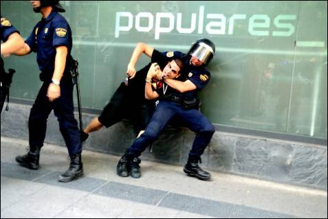 Un policía detiene a un manifestante contra los recortes del Gobierno en la sede del PP de Madrid, el 13 de julio de 2012.