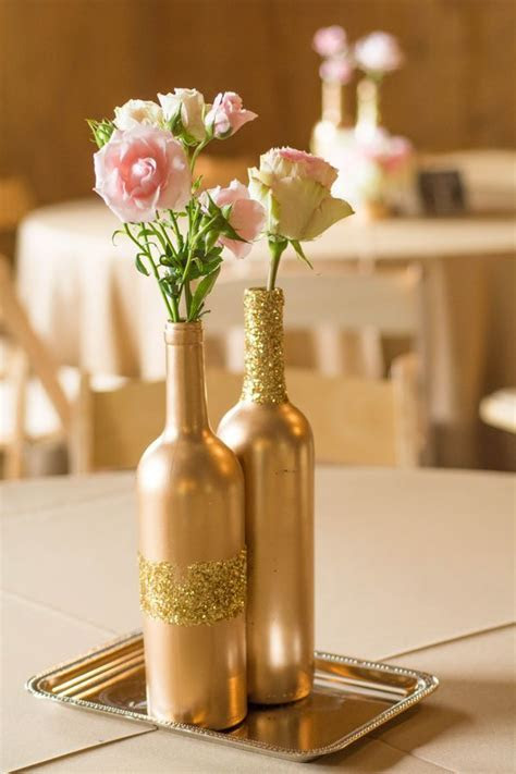 Gold wine bottles with flowers as centerpieces for
