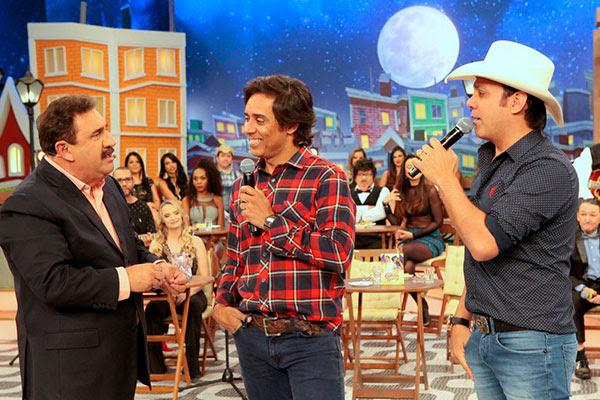 A dupla Guilherme e Santiago conversa com o apresentador Ratinho no palco do programa