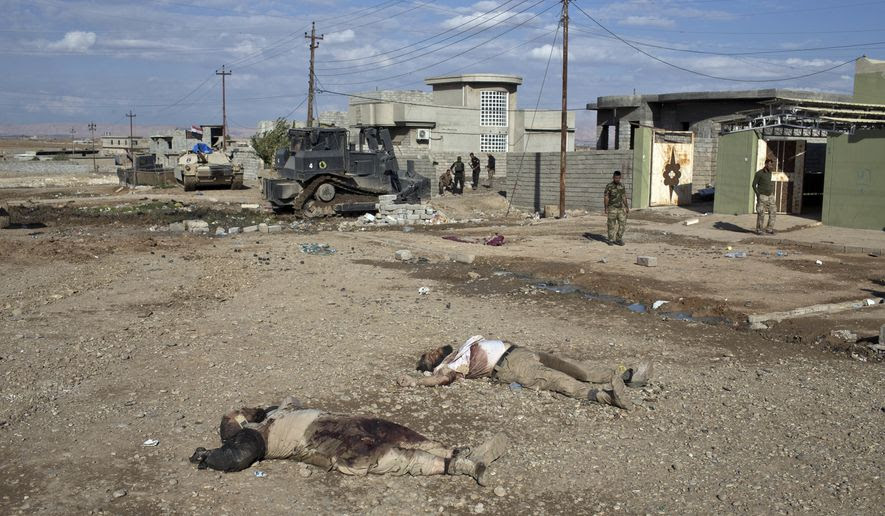EDS NOTE: GRAPHIC CONTENT -- The bodies of two Islamic State militants lay on a street in Gogjali, an eastern district of Mosul, Iraq, Wednesday, Nov. 2, 2016. Iraqi special forces paused their advance in the eastern district of Mosul on Wednesday to clear a neighborhood of any remaining Islamic State militants, killing at least eight while carrying out house-to-house searches. (AP Photo/Marko Drobnjakovic)