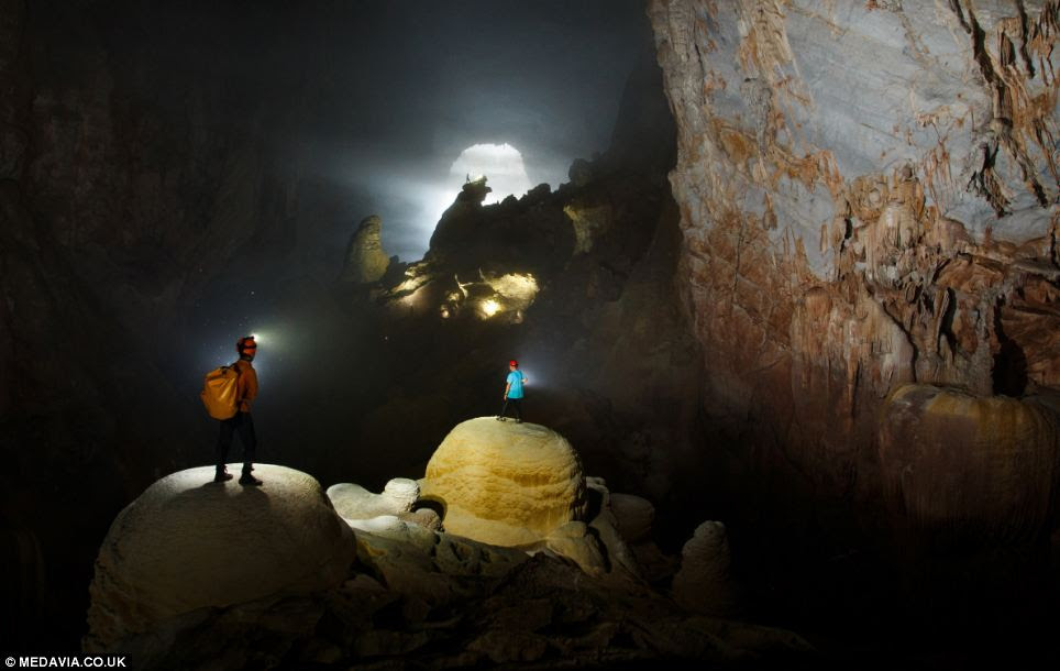 Howard and Deb Limbert, in the foreground, look on as a tourgroup member explores the cave in the distance