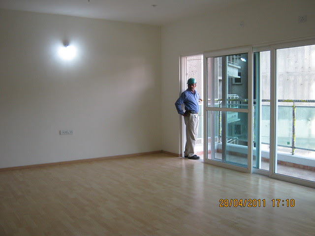 Spacious living with wooden flooring and sliding door of the balcony in  Sangria Towers at Megapolis Hinjewadi Phase 3, Pune