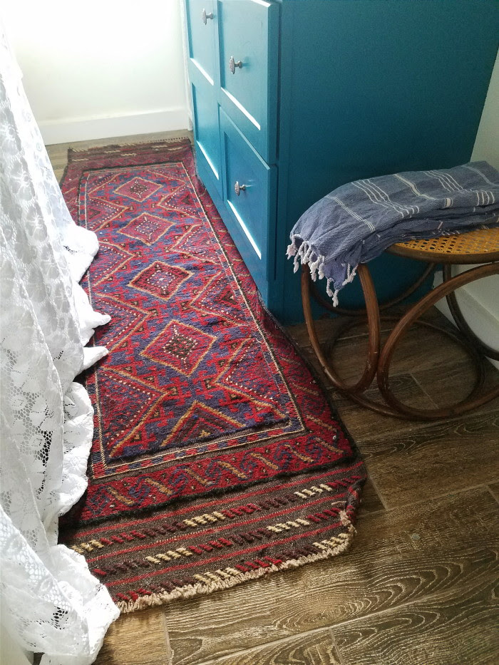 Vintage middle eastern rug with maroon and navy: a vintage bohemian bathroom