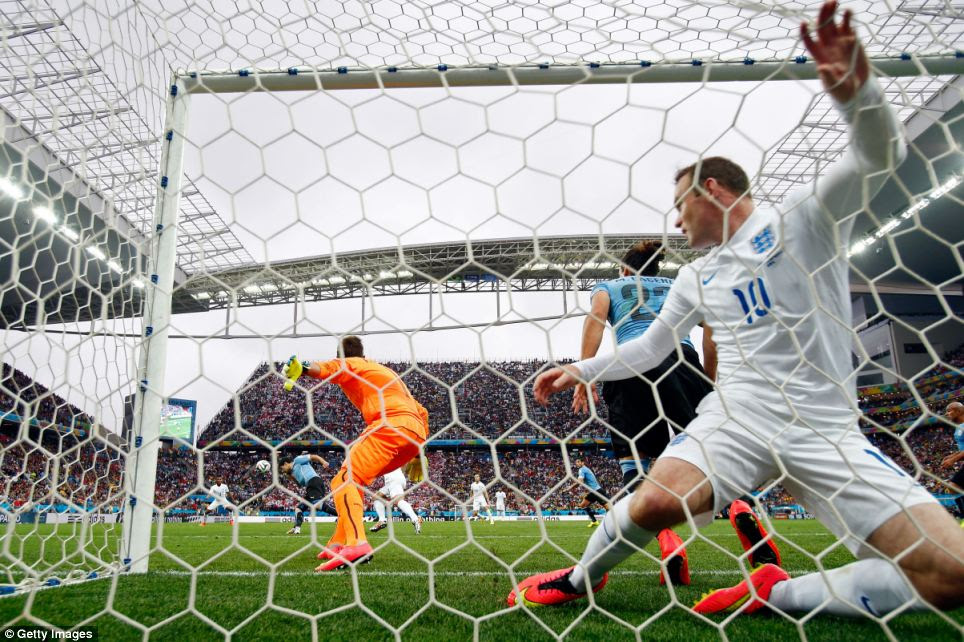 Battling on: Wayne Rooney of England falls into the net after his header went off the crossbar