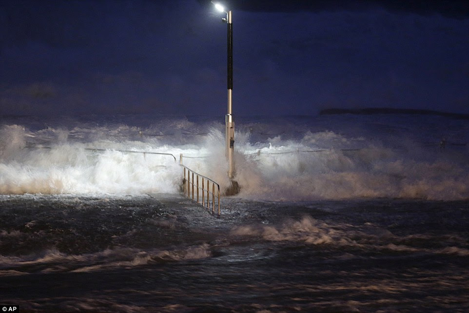 Huge waves crash over swimming baths at Avalon Beach in Sydney as the storm rages on