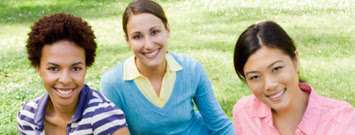Photo: Three women sitting on grass and smiling