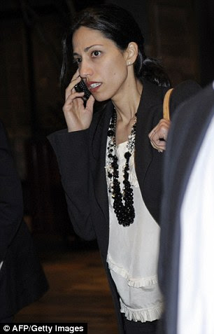 Talking: Huma Abedin, aide to US Secretary of State Hillary Clinton, and wife of embattled Weiner is on the phone as the delegation leaves Ethiopia's Prime Minister Meles Zenawi's compound on Monday
