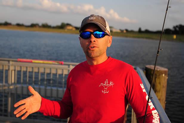 photo of a man speaking on a dock near fishing gear