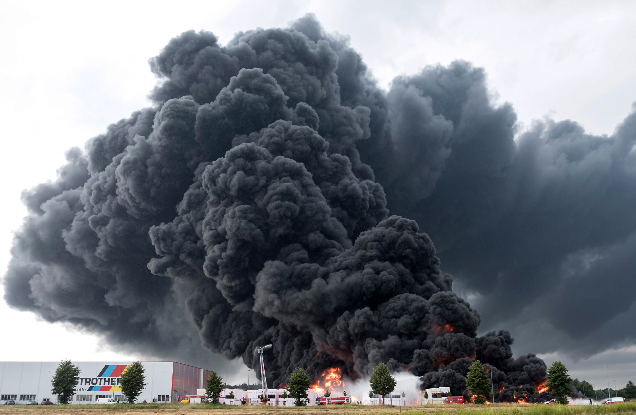 epa05443258 Thick smoke spreads over a burning Styrofoam site while firefighters attempt to put it out in Wittenberge, Germany, 27 July 2016. According to initial information, no one was injured in the factory from Austrian insulation company Austrotherm. Lightning set the giant Styrofoam site on fire and caused millions of euros worth of damage.  EPA/JENS WEGNER