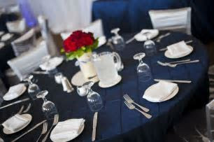 Navy blue pin tuck table linen with silver chair covers. #