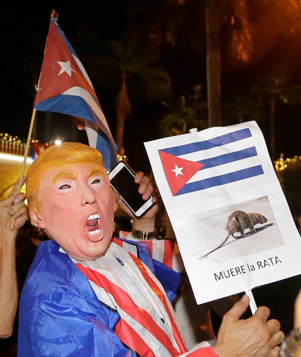 """Uma pessoa usando uma máscara de Donald Trump prende um sinal em espanhol que lê, """"The Rat morre."""""""