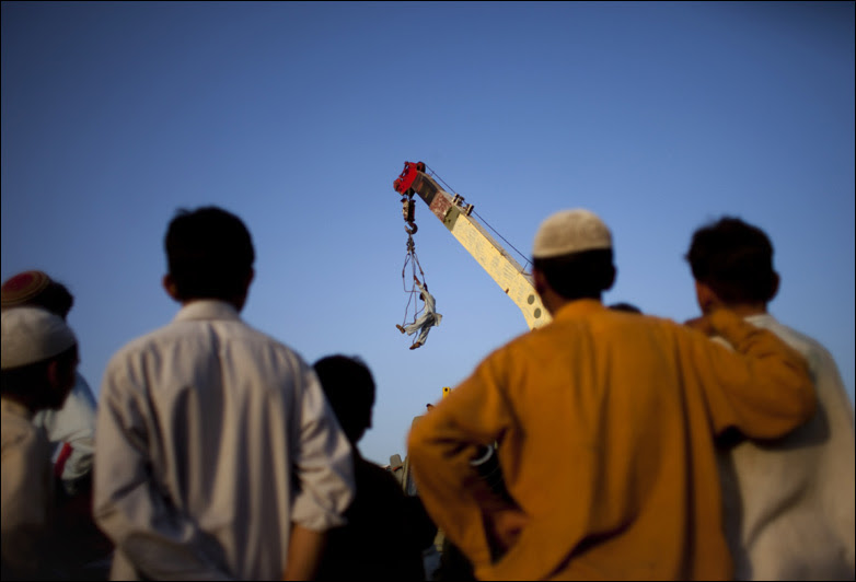 A Pakistani worker is lifted by a crane to unload a container