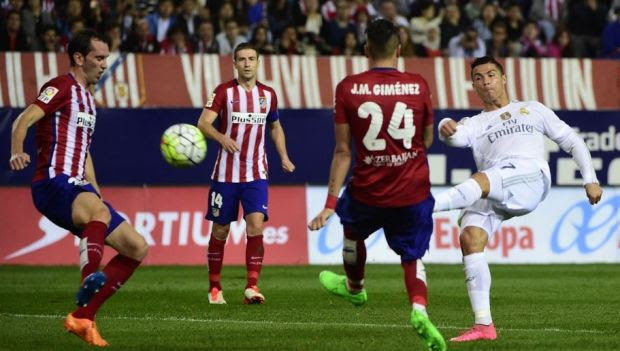 Real Madrid's Portuguese forward Cristiano Ronaldo (R) kicks the ball past Atletico Madrid's Uruguayan defender Diego Godin (L) during the Spanish league football match Club Atletico de Madrid vs Real Madrid CF at the Vicente Calderon stadium in Madrid on October 4, 2015. AFP PHOTO/ PIERRE-PHILIPPE MARCOU (Photo credit should read PIERRE-PHILIPPE MARCOU/AFP/Getty Images)