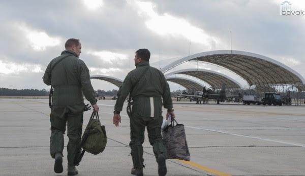 El teniente coronel Jeffrey Hogan, piloto instructor en la A-29 de la USAF, hablar con el piloto afgano (derecha) como caminan hacia aviones Super Tucano en Moody Air Force Base. (Foto: Airman 1st Class Ceaira Tinsley / USAF)