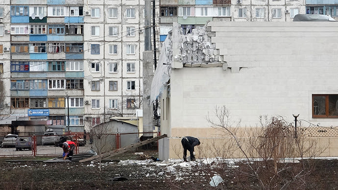 People remove debris near the building damaged by shelling on Saturday in Mariupol, eastern Ukraine, January 25, 2015 (Reuters / Nikolay Ryabchenko)