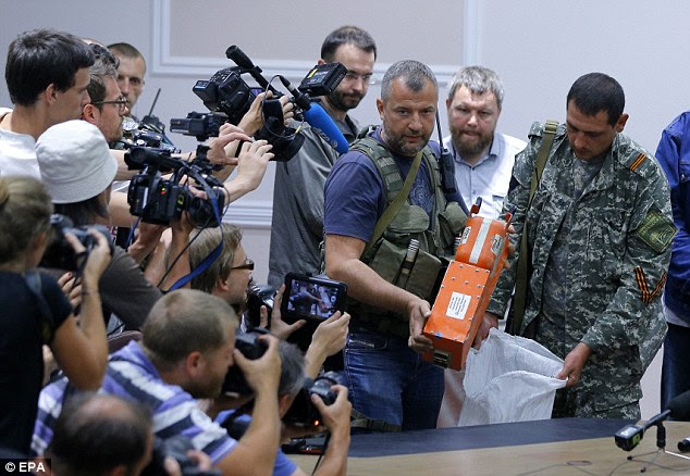 Crucial evidence: Pro-Russian separatists finally hand over the two black boxes from MH17 to Colonel Mohamed Sakri (not pictured) of Malaysian National Security Council during a press conference in Donetsk