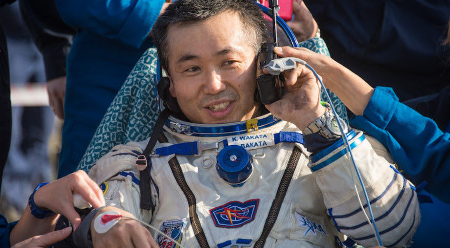 Expedition 39 Commander Koichi Wakata of  JAXAtalks on a satellite phone in a chair outside the Soyuz Capsule just minutes after he and Soyuz Commander Mikhail Tyurin and Flight Engineer Rick Mastracchio of NASA, landed in their Soyuz TMA-11M spacecraft in Kazakhstan in May 2014. Credit: NASA/Bill Ingalls